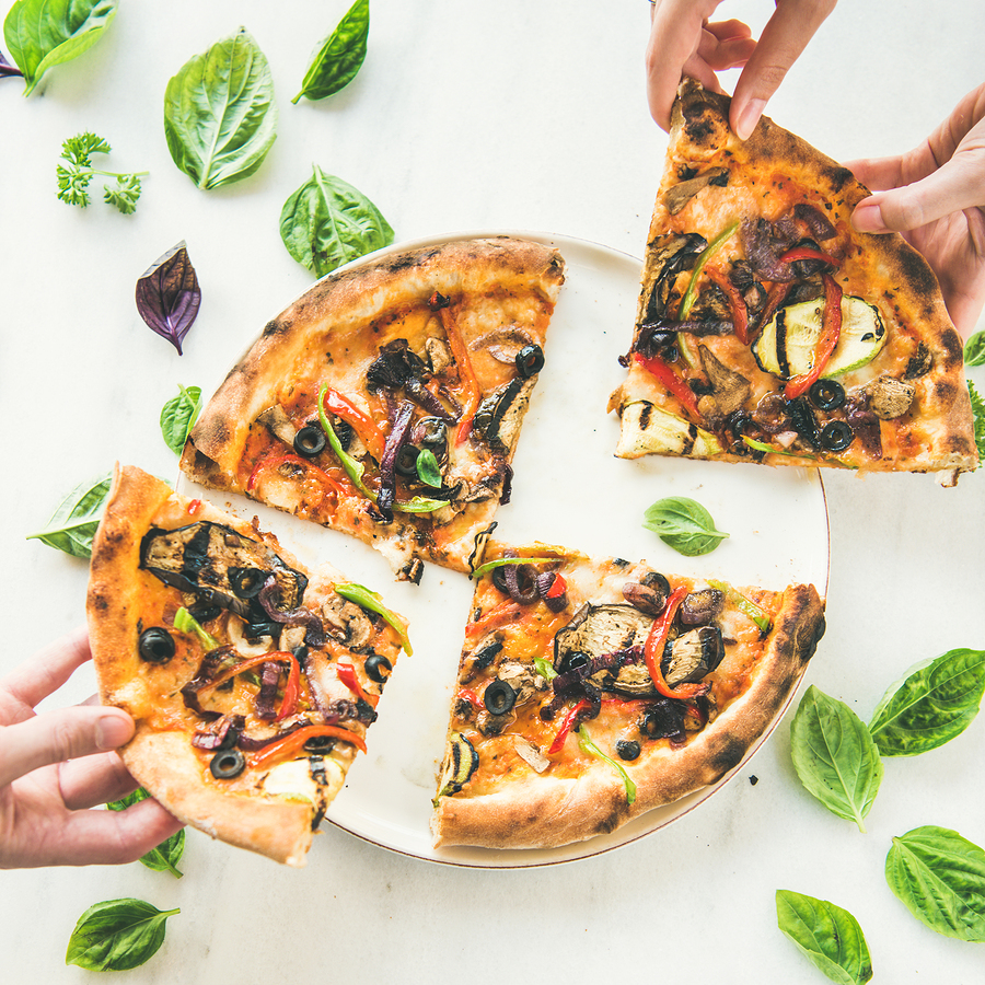 Peoples Hands Taking Freshly Baked Vegetarian Pizza Over Marble