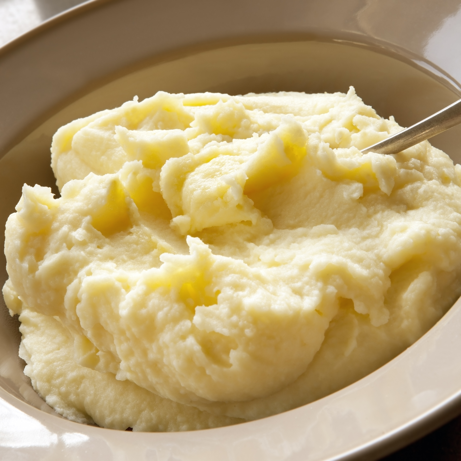 Mashed potato with spoon, in serving bowl.