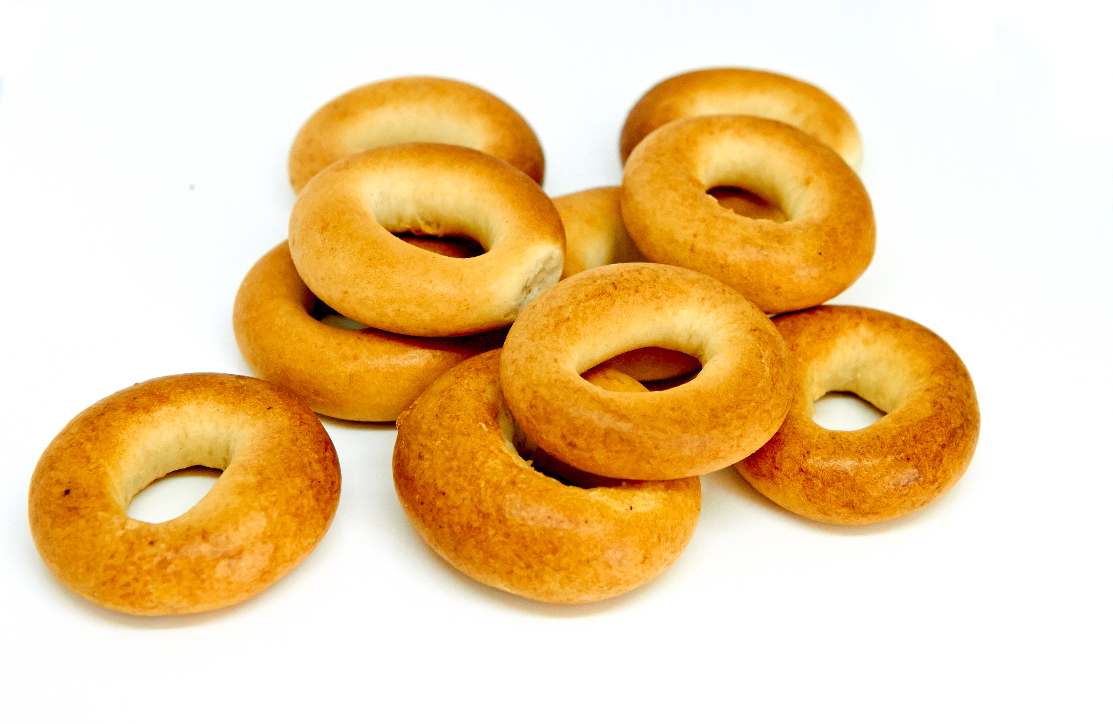 Stack Of A Dozen Golden Brown Bagels In A Variety Of Flavors. Ev